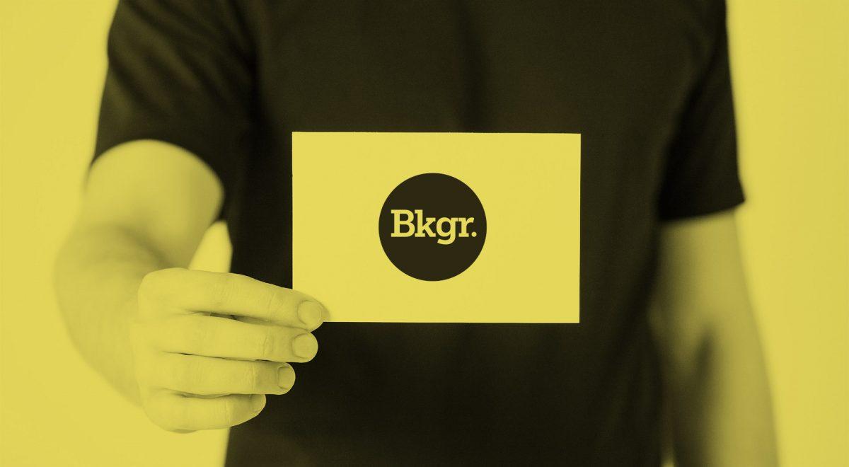 man håller fram ett kort som talarstöd med företaget Backgrounds logotyp på