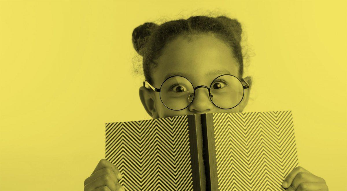 Flicka med glasögon håller upp en bok framför ansiktet