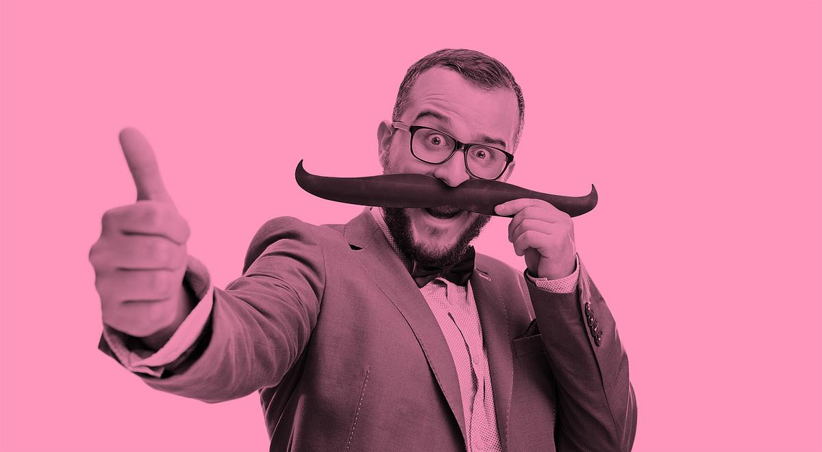 Man i kostym som gör tumme upp och håller upp en överdimensionerad mustasch framför sitt ansikte